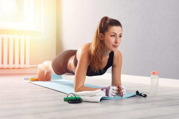 Mulher no desgaste de fitness fazendo exercícios em casa. é hora de fazer ioga. garota saudável fazendo exercícios enquanto descansava em casa. fitness, relaxamento, conceito de ficar em casa