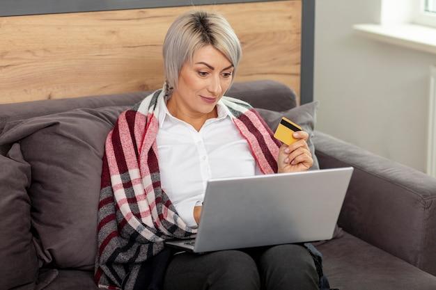 Mulher no escritório com laptop e cartão de crédito