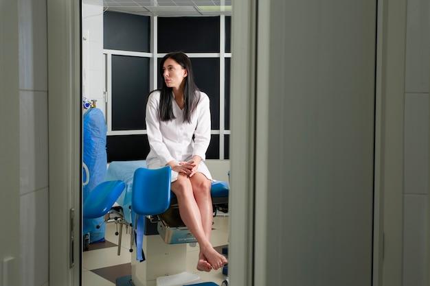 Mulher no escritório do ginecologista sentado e esperando por um médico com resultados dos testes, vista através de uma porta