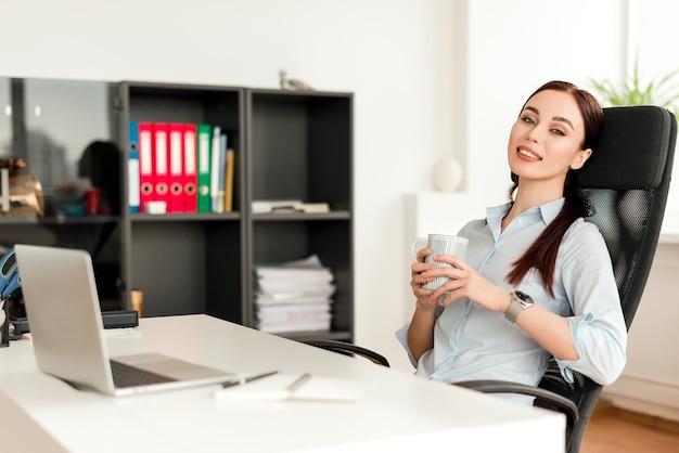 Mulher no escritório em um local de trabalho atrás de sua mesa trabalhando e bebendo xícara de chá
