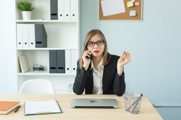 Mulher no escritório falando ao telefone