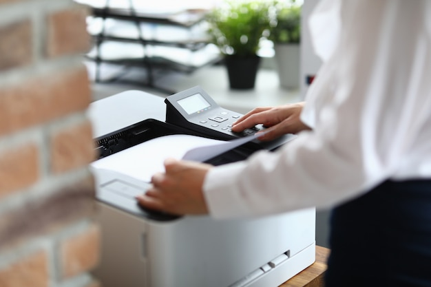 Mulher no escritório imprime documentos na impressora