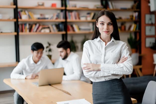 Mulher no escritório trabalha com equipe de colegas de trabalho na mesa