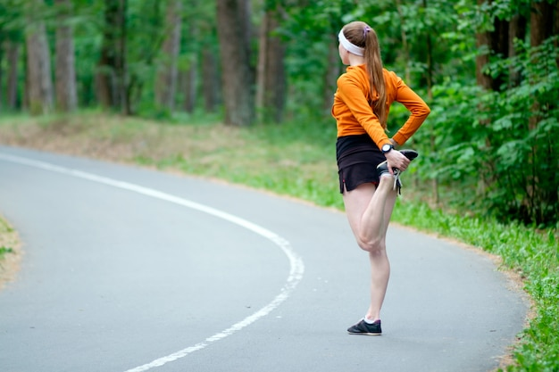 Mulher no esporte laranja hoody aquecendo antes de correr