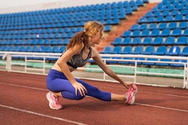 Mulher no estádio, estendendo-se antes de correr