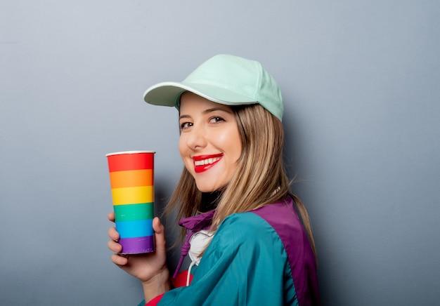 Mulher no estilo de roupa dos anos 90 com copo de bebida