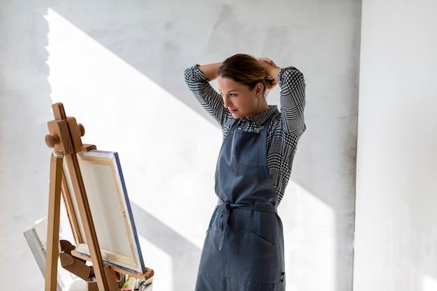 Mulher no estúdio com lona e cavalete