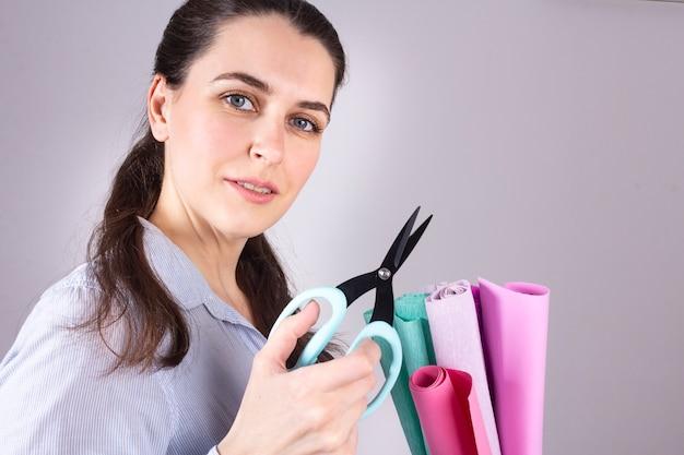 Mulher no estúdio diy que guarda tesouras e rolos da tela. faça o projeto de artesanato. scrapbook, costura, feltro, passatempo quilting.