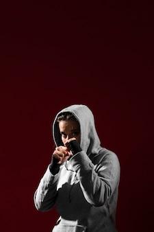Mulher no fundo cinzento do espaço do hoodie e da cópia