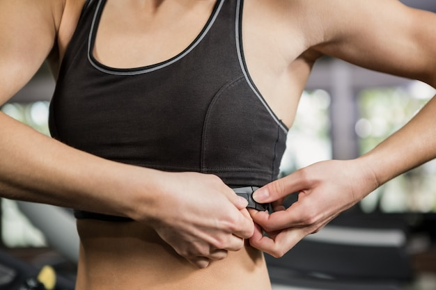 Mulher no ginásio usando monitor de freqüência cardíaca em volta do peito