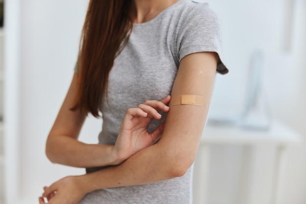 Mulher no hospital com fita adesiva na imunidade à saúde do ombro