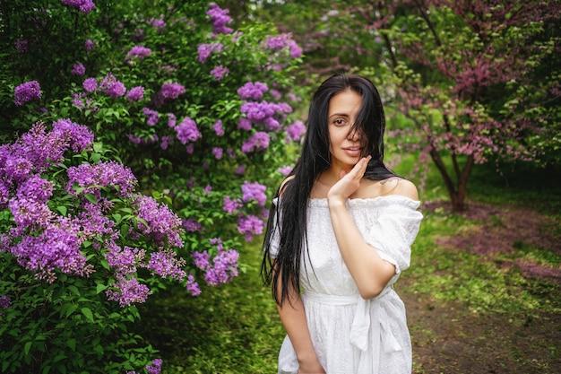 Mulher no jardim florido. os cabelos dela tremulam com o vento. foto em movimento