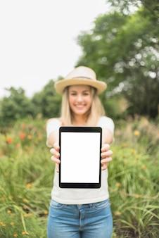 Mulher no jardim mostrando tablet com tela em branco