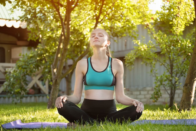 Mulher no jardim pratica ioga. manhã de verão.