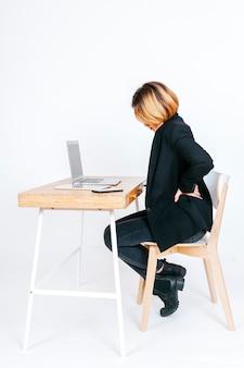 Mulher no local de trabalho com problemas de coluna