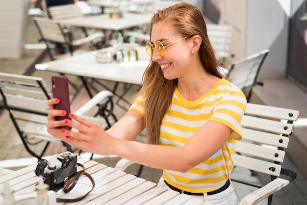 Mulher no meio da foto na mesa tirando selfie
