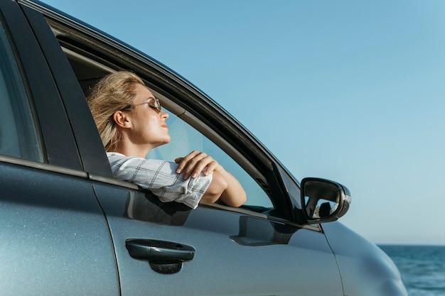 Mulher no meio de um carro olhando para o mar