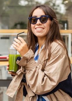 Mulher no meio do tiro bebendo smoothie verde
