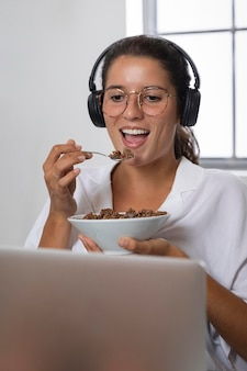 Mulher no meio do tiro comendo na frente do laptop