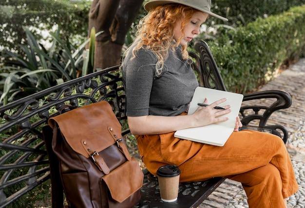 Mulher no meio do tiro no banco escrevendo no diário