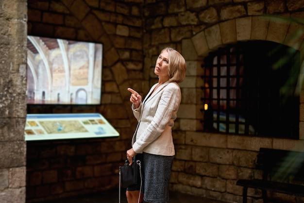 Mulher no museu usa guia eletrônico do monitor touchscreen, conceito da educação moderna