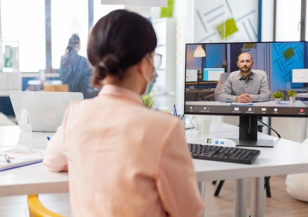 Mulher no novo escritório normal ouvindo homem falando durante a videoconferência online, olhando para a tela que discute o projeto durante o surto de gripe coronavírus.