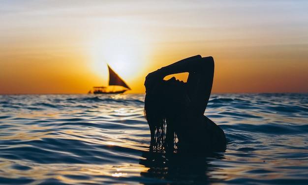 Mulher no oceano no tempo do por do sol