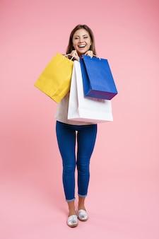Mulher no olhar básico, segurando sacos depois de fazer compras no shopping