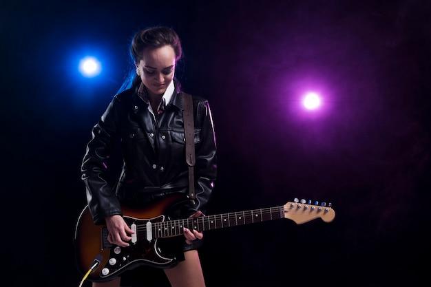 Mulher no palco com luzes tocando violão