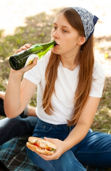 Mulher no parque bebendo cerveja e comendo hambúrguer