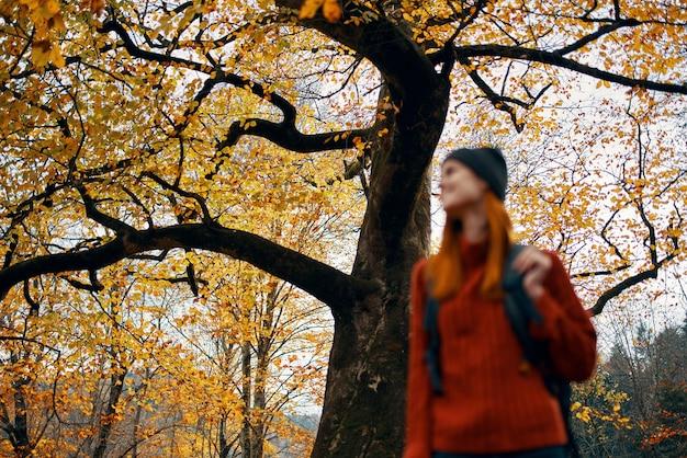 Mulher no parque com uma mochila nas costas relaxa ao ar livre em uma paisagem de árvores altas