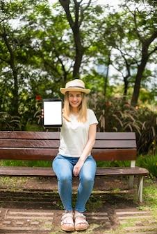 Mulher no parque mostrando tablet com tela em branco
