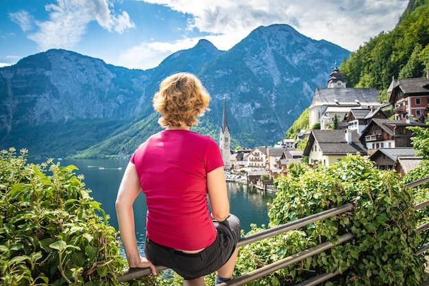 Mulher no ponto de vista no hallstat austríaco no verão, apreciando a bela vista do lago, cidade e montanhas