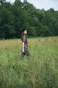 Mulher no prado natureza caminha pelo campo no contexto de árvores liberdade