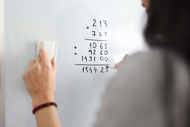 Mulher no quadro branco adiciona conceito de treinamento online de números matemáticos
