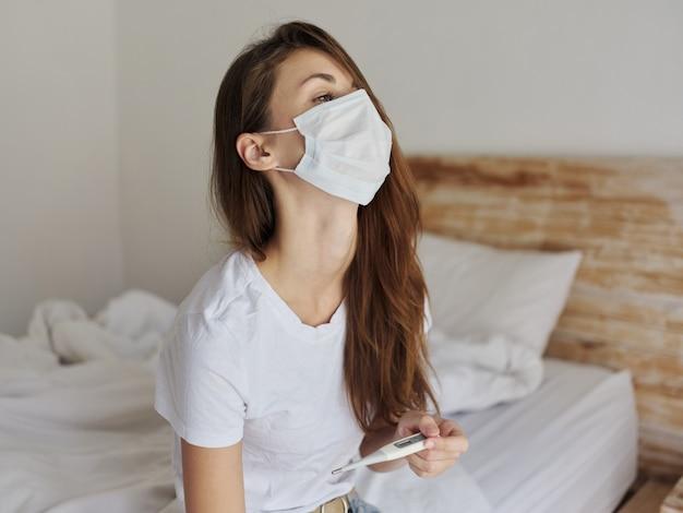 Mulher no quarto com uma máscara médica e um termômetro nas mãos