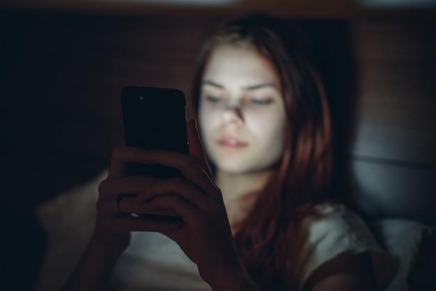 Mulher no quarto deitada na cama com um telefone nas mãos. vício