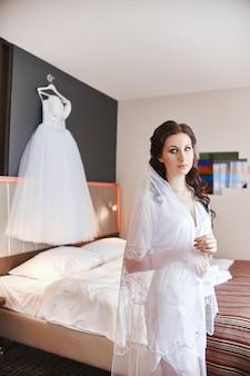 Mulher no quarto em um roupão de banho fica no de seus vestidos de noiva
