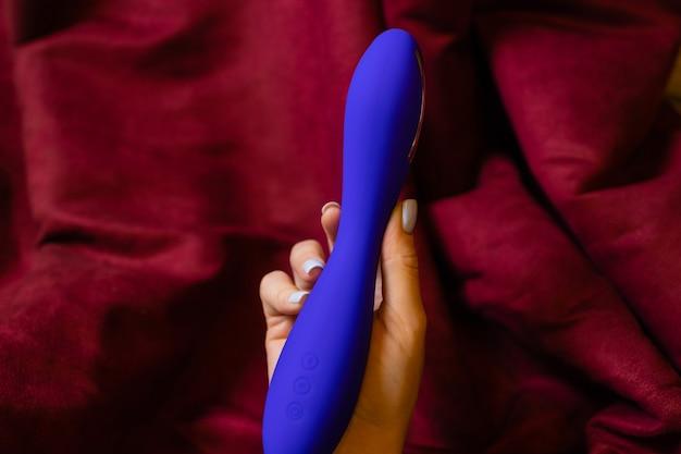 Mulher no quarto segurando o vibrador