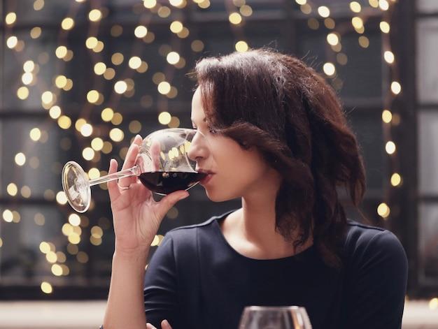 Mulher no restaurante bebendo um copo de vinho