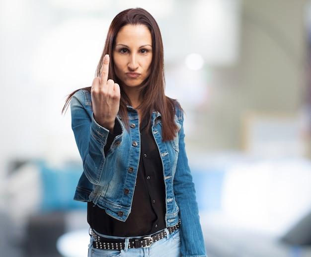Mulher no revestimento do denim fazendo um gesto com a mão ofensiva
