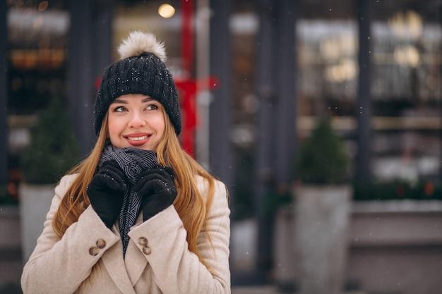 Mulher no revestimento do lado de fora do café em uma rua de inverno