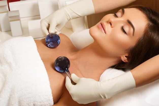 Mulher no salão de beleza durante o tratamento com bolas de vidro frio