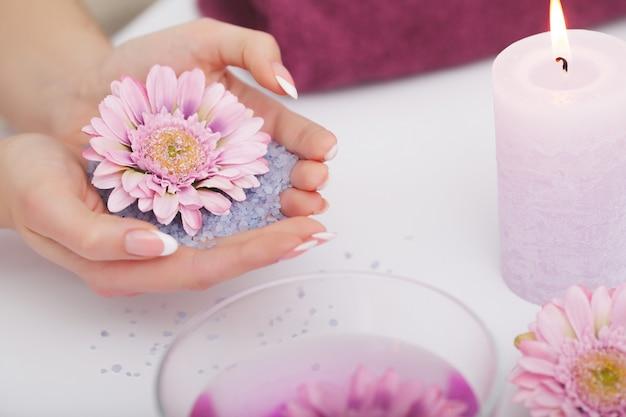 Mulher no salão de beleza que guarda os dedos no banho do aroma para as mãos.