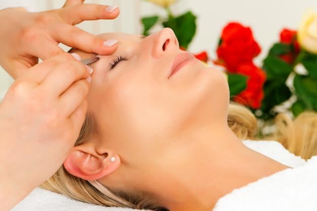 Mulher no salão de beleza recebe as sobrancelhas aparadas