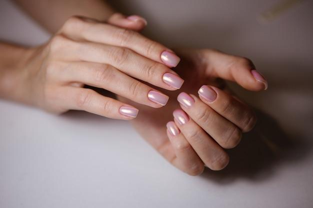 Mulher no salão de beleza recebendo manicure por esteticista de unhas