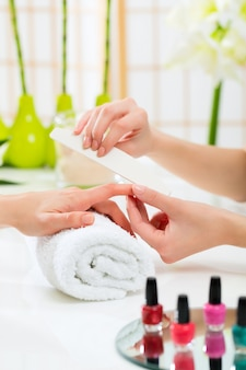 Mulher no salão de beleza recebendo manicure