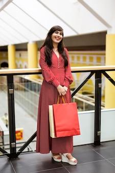 Mulher no shopping posando com sacolas de compras