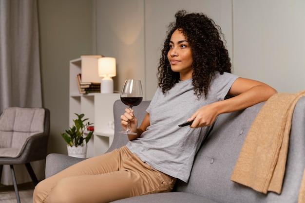 Mulher no sofá assistindo tv e bebendo vinho