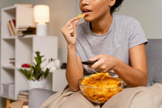 Mulher no sofá assistindo tv e comendo batatinhas